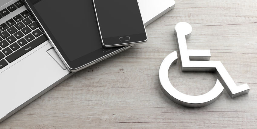 A wheelchair placard next to a laptop and cellphone, implying digital accessibility