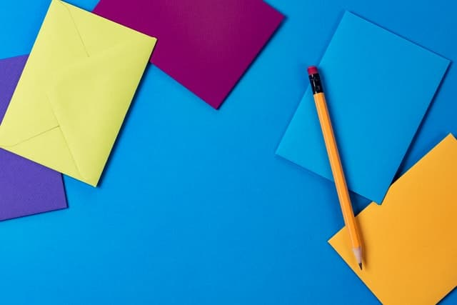 an array of colorful notepads on a blue surface